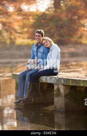 Feliz joven y su novia en el muelle de pesca