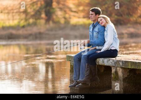 Pareja joven tranquila junto al estanque de pesca en otoño