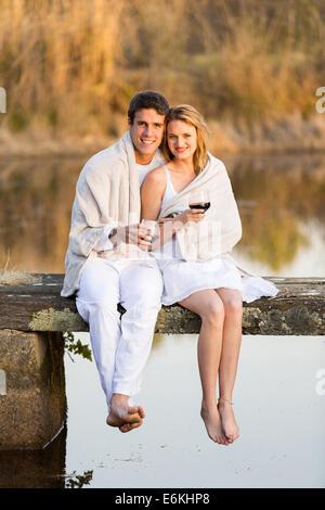 Pareja romántica sentado en el muelle y bebiendo vino al atardecer