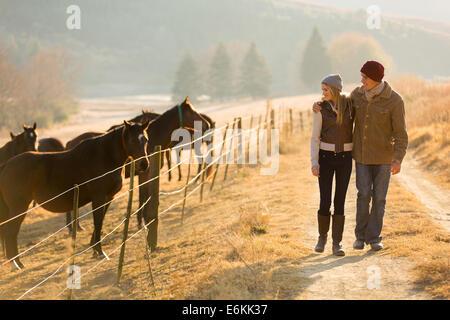 Pareja joven caminando en la granja de caballos