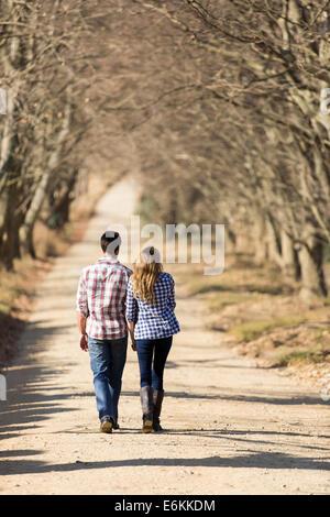 Vista posterior de la entrañable pareja joven caminando en el país por carretera en otoño