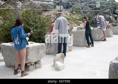 Los escultores trabajan en piedra de Portland local en una comunidad open air studio espacio a Tout Cantera, Isla Foto de stock