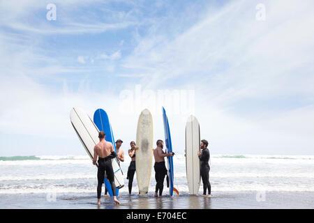 Un grupo de amigos surfistas masculinos y femeninos de pie en la playa con tablas de surf