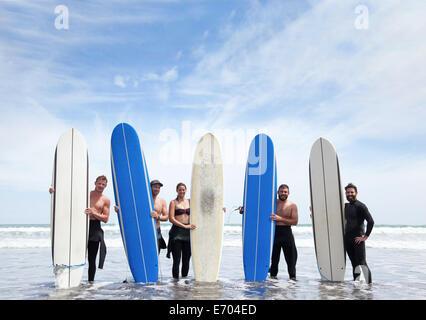 Retrato de grupo de amigos surfistas masculinos y femeninos de pie en el mar con tablas de surf