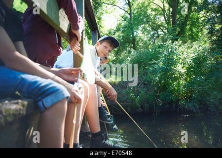 Los niños sentados en el puente, pesca