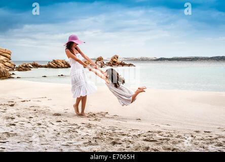 Joven hija oscilante en la playa, La Maddalena, Cerdeña, Italia Foto de stock