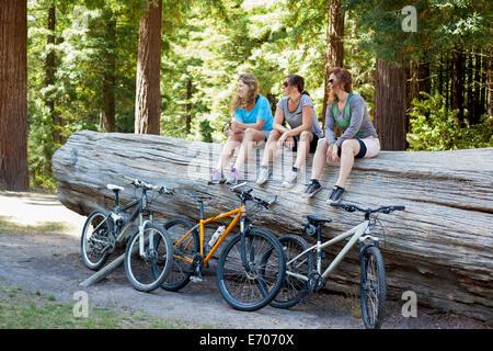 Tres mujeres ciclistas de montaña sentado en el tronco del árbol en el bosque