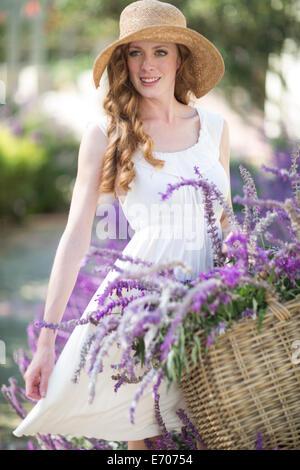 Retrato de joven bella en el jardín con cesta de flores púrpura