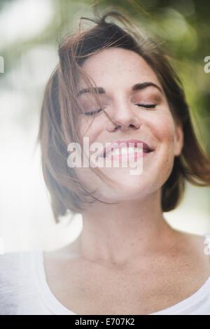 Close Up retrato de mujer adulta media sonriente con los ojos cerrados