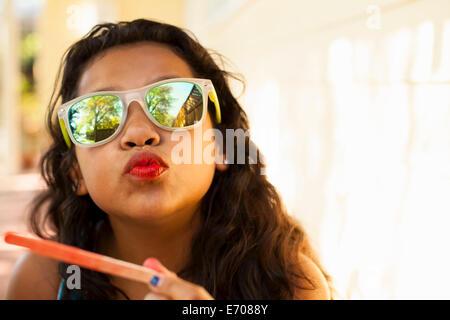 Retrato de chica con labios rojos y ice lolly stick tirando rostro