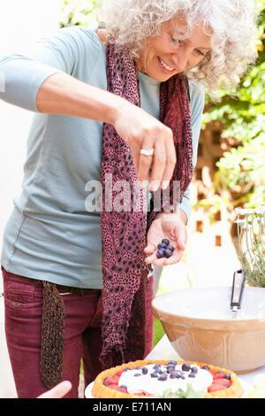 Mujer madura preparar flan de frutas en garden party