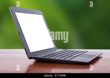 Tablet portátil con pantalla en blanco blanco sobre la mesa de madera, vista lateral, natural de fondo verde.