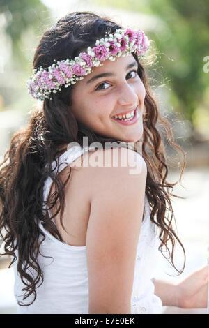 Sonriente joven adolescente con flores en su cabello