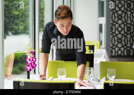 Tabla de configuración de camarero asiática en el restaurante