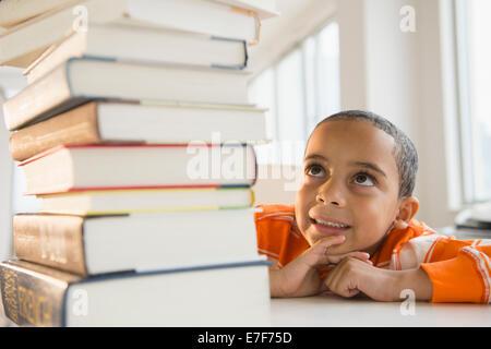 Mestizos niño mirando hacia arriba en la pila de libros