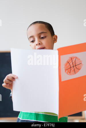 Mestizos chico leyendo informe sobre baloncesto en clase