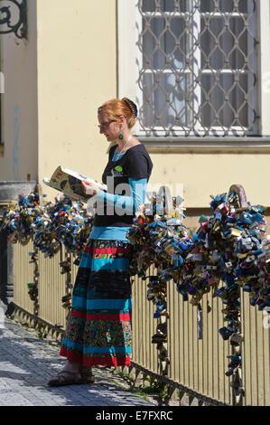 Un agente del Segway principales contra la barandilla de un puente cubierto con una serie de candados cerrados, Praga, República Checa.