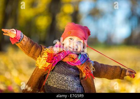 Niña feliz jugando en el parque de otoño