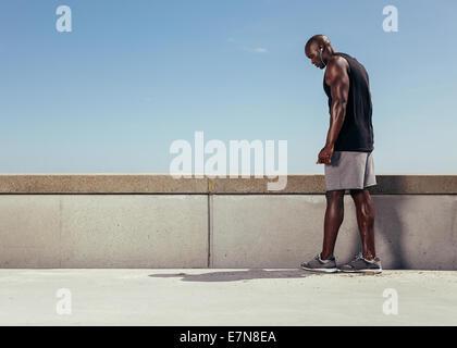 Imagen joven muscular sobre una pasarela preparándose para su carrera. Centrado atleta masculino se preparaba para su ejecución entrenar al aire libre