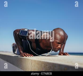 Imagen del hombre deportivo haciendo push-ups. Fuerte joven modelo fitness el ejercicio. Modelo masculino africano entrenar al aire libre. Foto de stock