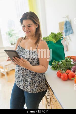 Mujer con tablet PC en la cocina