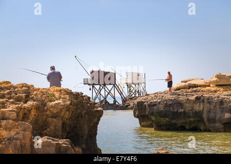 Dos de pesca pescador rocks off con pescadores tradicionales cabañas sobre pilotes, con redes de carrelets en la costa de Charente Maritime en Francia. Foto de stock