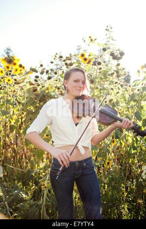 Mujer joven tocando el violín en campo de girasol