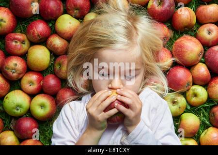 Niña acostada sobre la hierba verde para comer manzanas rojas Foto de stock