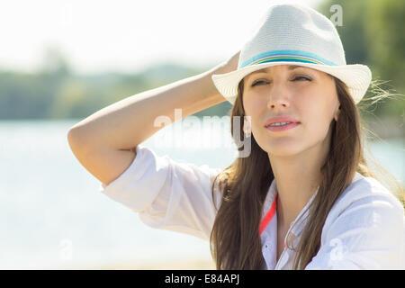 Hermosa chica hipster en hat cerca del río. Joven mujer caucásica posando en la playa.