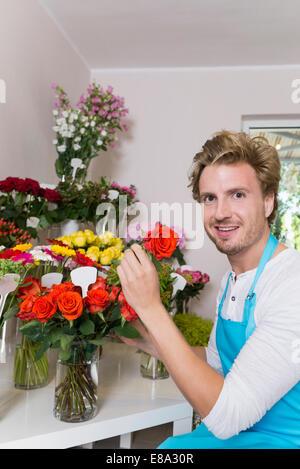 Retrato de un hombre adulto medio arreglar las flores en un jarrón, sonriendo