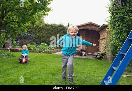 Hermano mayor tirando de la hermana en coche de juguete en el jardín