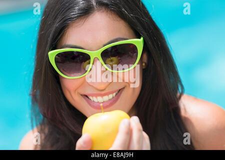 Retrato de mujer joven en piscina mantiene apple