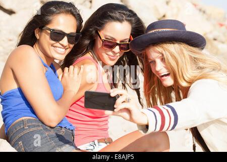 Tres jóvenes mujeres teniendo selfie smartphone en beach, Malibu, California, EE.UU.