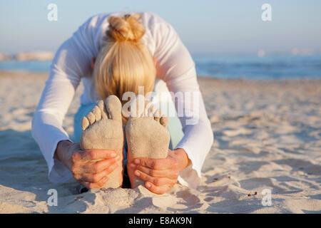 Mujer haciendo yoga estiramiento de oración en la playa