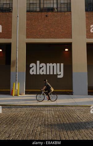 Messenger masculino en bicicleta a lo largo de las aceras de la ciudad