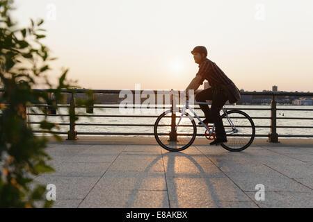 Messenger masculino en bicicleta a lo largo de city riverside