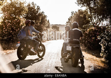 Vista trasera de cuatro amigos en motocicletas chateando en caminos rurales, Cagliari, Cerdeña, Italia Foto de stock