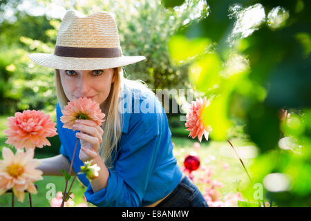 Retrato de mujer adulta media oliendo flores de jardín