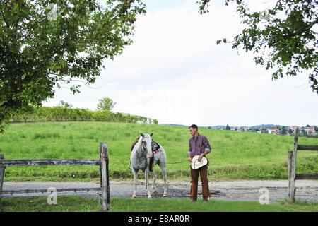 Joven vaquero caballo líder de marcha a través de la puerta de enlace
