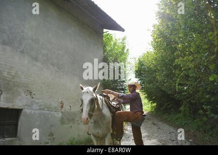 Joven en el montaje del engranaje cowboy Horse Barn exterior