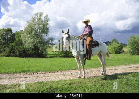 Retrato de joven en marcha cowboy a caballo sobre la pista de tierra
