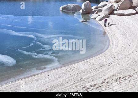 Mujer con perro caminando a lo largo de la playa y el lago congelado, Colorado, Estados Unidos