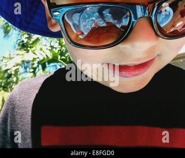 Retrato de un niño parado en una piscina infantil con gafas de sol