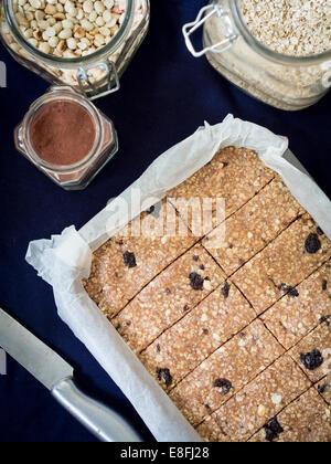 Granola masticable (muesli casero) Barras de Proteína de maní, miel, nueces y pasas sobre un papel de hornear. Vista desde arriba.