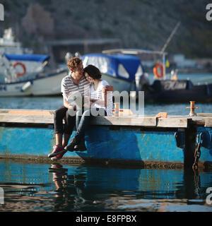 La pareja de adolescentes (14-15) sentados en el malecón, abrazando