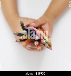 Las manos del muchacho la celebración de lápices de colores