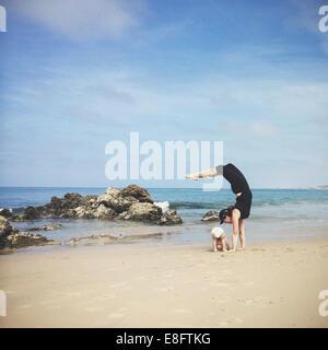 Madre e hijo hacer yoga en la playa, California, Estados Unidos, EE.UU.