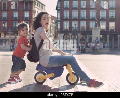 Niño empujando a su madre en un triciclo de juguete