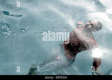 Mujer completamente vestida con sus ojos cerrados nadando bajo el agua en una piscina Foto de stock