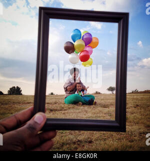 Hombre sosteniendo un cuadro delante de una madre y un hijo en un prado, Roodeport, Johannesburgo, Gauteng, Sudáfrica